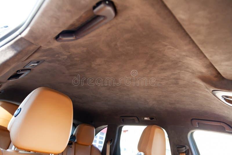 O teto do carro de SUV puxado pelo alkantara material macio marrom na oficina para ajustar e denominar o interior, vista de fotos de stock royalty free
