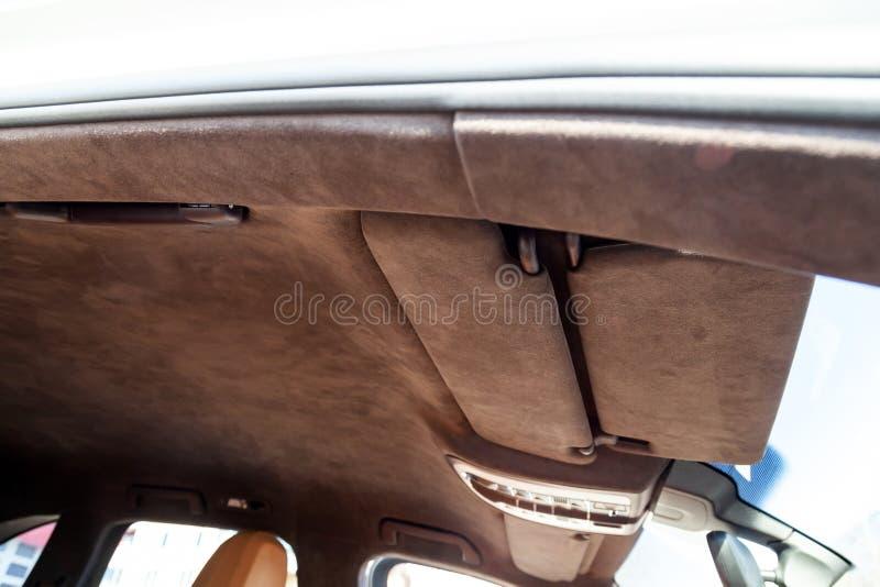 O teto do carro de SUV puxado pelo alkantara material macio marrom na oficina para ajustar e denominar o interior, vista de imagens de stock
