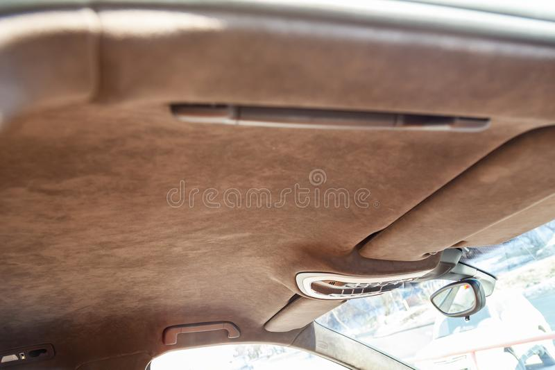 O teto do carro de SUV puxado pelo alkantara material macio marrom na oficina para ajustar e denominar o interior, vista de imagem de stock