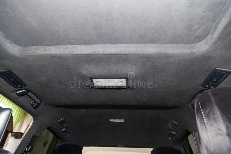 O teto do carro de SUV puxado pelo alkantara material macio preto na oficina para ajustar e denominar o interiorof imagem de stock
