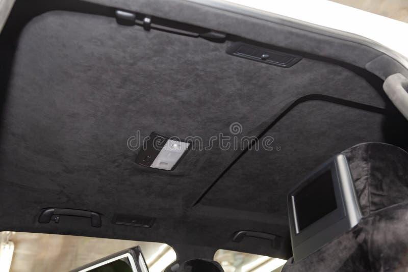 O teto do carro de SUV puxado pelo alkantara material macio preto na oficina para ajustar e denominar o interiorof fotografia de stock