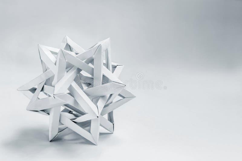 O tetraeder complexo dobrou o origâmi de papel em um fundo branco fotografia de stock
