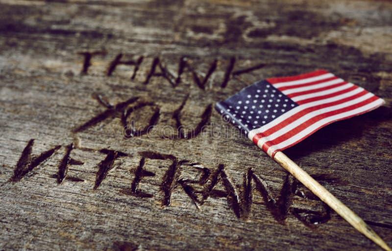 O texto agradece-lhe veteranos e a bandeira dos E.U. imagem de stock