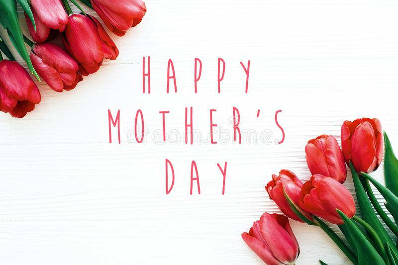 O texto feliz do dia de m?e e as tulipas vermelhas bonitas no fundo de madeira branco liso colocam Cart?o feliz do dia da m?e com imagens de stock