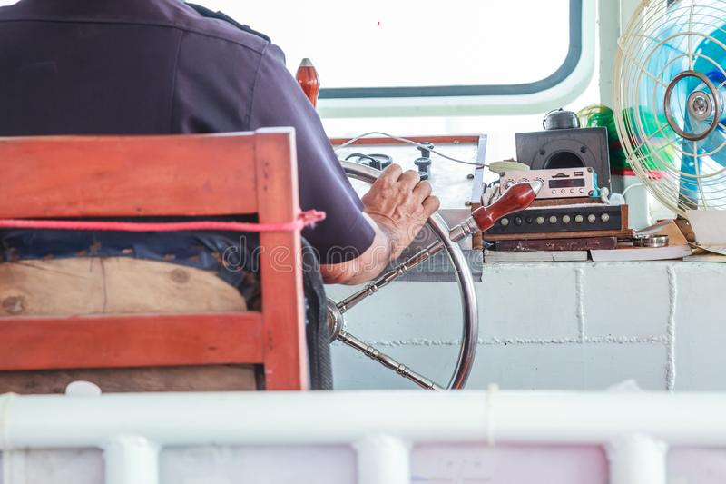 O timoneiro do navegador é responsável para a posição do ferryboat controlando o leme do volante, sternwheel na casa piloto fotos de stock