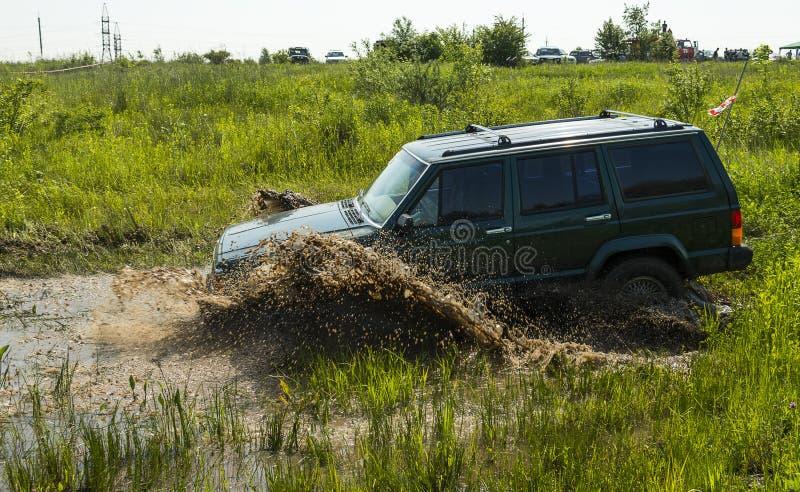 O tipo fora de estrada Jeep Cherokee do veículo supera um poço da lama fotos de stock royalty free