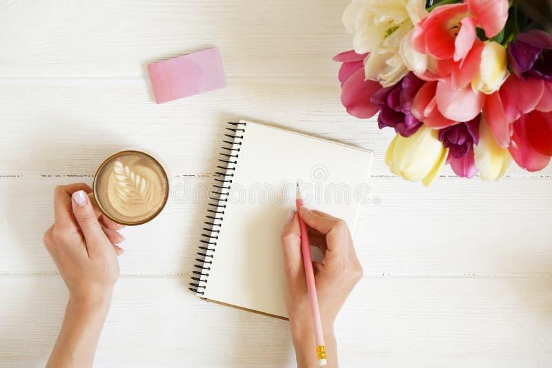 O tiro aéreo da mulher entrega o desenho, escrita com o lápis no caderno aberto, bebendo o café na tabela de madeira branca Tulip imagens de stock royalty free
