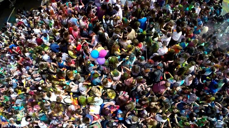 O tiro aéreo de uma mão de ondulação e de fundir do adolescente feliz da menina um beijo durante Holi colore o festival com segui fotografia de stock