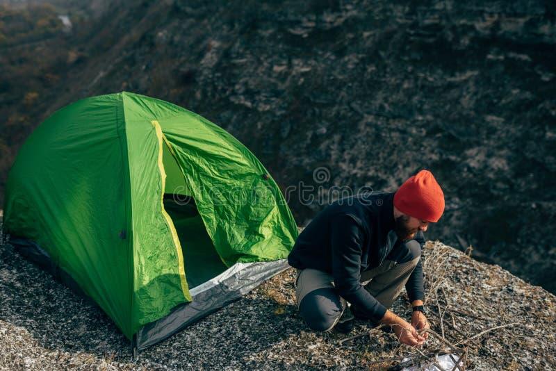 O tiro aéreo horizontal do ar livre do homem novo do caminhante prepara refeições matinais para a fogueira nas montanhas foto de stock royalty free