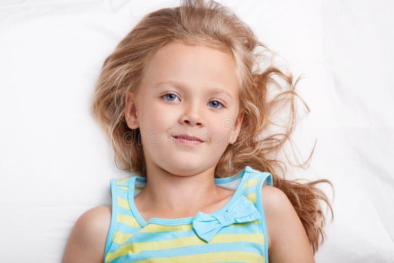 O tiro ascendente próximo da criança pequena eyed azul olha agradavelmente na câmera, veste o nightwear ocasional, tem o bom rest imagem de stock royalty free
