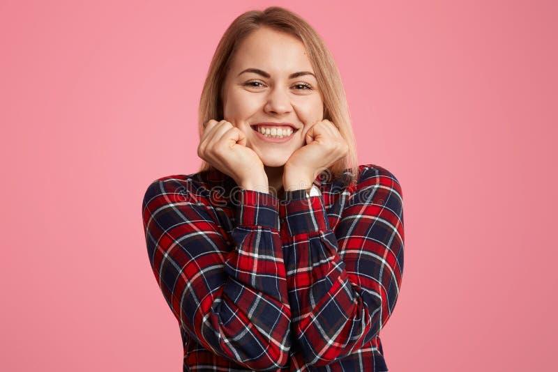 O tiro ascendente próximo da mulher satisfeita guarda o queixo, sorri amplamente, mostra os dentes perfeitos brancos, sendo no bo imagem de stock royalty free