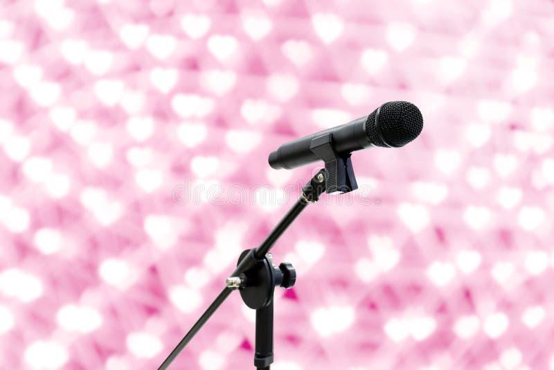 O tiro ascendente próximo do microfone em romântico bonito ou no brilho do fundo do rosa do bokeh do coração do borrão ilumina a  fotografia de stock royalty free