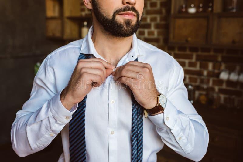 o tiro colhido da asseguração do homem de negócios abotoa-se na camisa imagens de stock royalty free