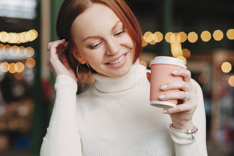 O tiro colhido da mulher de vista agradável levanta no café exterior, guarda a xícara de café do papel, vestida no equipamento br foto de stock