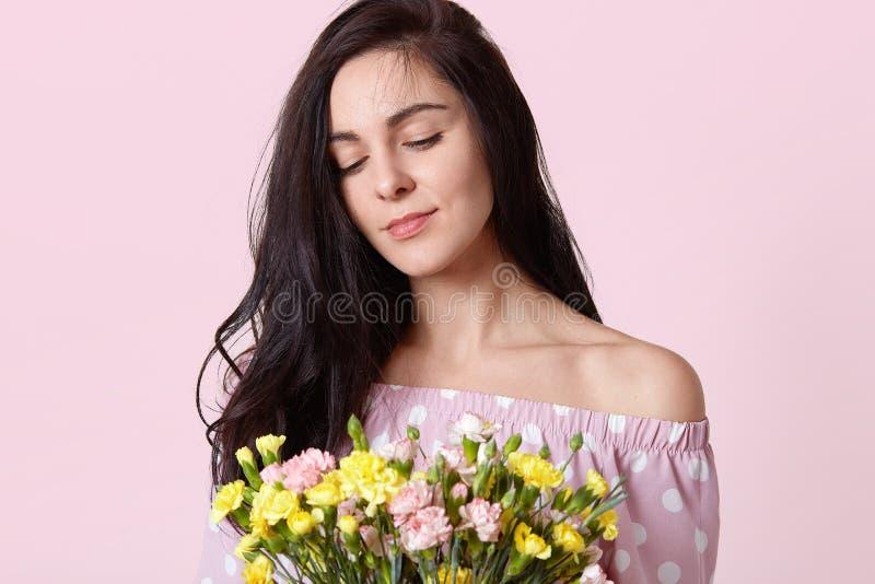 O tiro colhido da mulher parecendo jovem agradável com cabelo escuro, vestido no vestido do às bolinhas, guarda o ramalhete de am imagens de stock royalty free