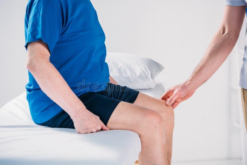 o tiro colhido da verificação do terapeuta da reabilitação superior equipa o joelho foto de stock