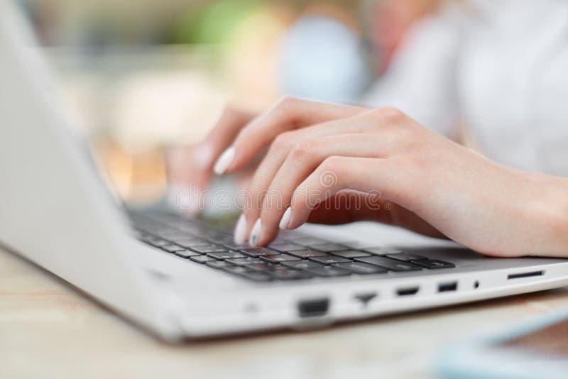 O tiro colhido das mãos fêmeas com os teclados agradáveis no laptop, trabalhos do tratamento de mãos da casa, senta-se na tabela  fotografia de stock royalty free