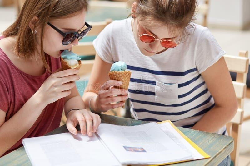 O tiro colhido de fêmeas novas focalizadas sérias olha atentamente no menu do bar, come o gelado frio do fruto, recreat durante a fotografia de stock royalty free