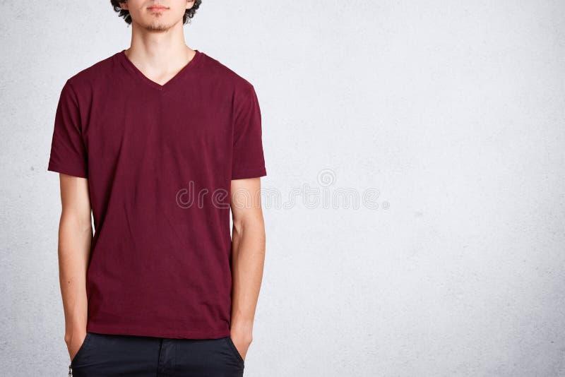 O tiro colhido do homem irreconhecível mantém as mãos no bolso, veste a camisa ocasional de t com espaço vazio da cópia para seu  imagem de stock royalty free