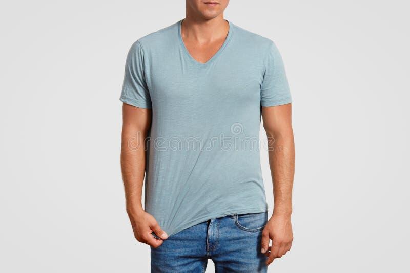 O tiro colhido do homem muscular na camisa de t e nas calças de brim ocasionais, suportes contra o fundo branco, mostra o espaço  fotografia de stock royalty free