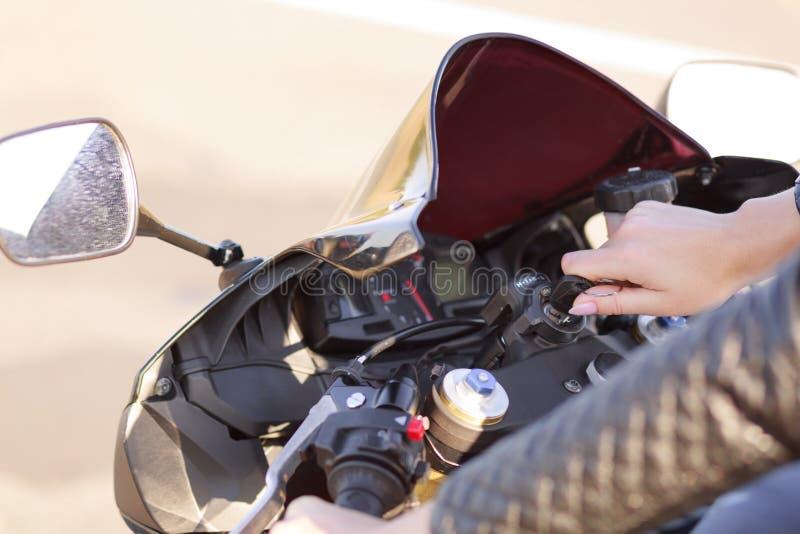 O tiro colhido do motociclista fêmea ativo irreconhecível tenta ligar o motor, gerencie na chave, cobre a grande distância na est imagens de stock