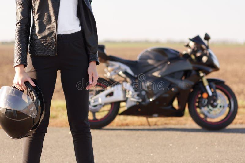 O tiro colhido do motociclista irreconhecível da mulher vestido em sportsclothes pretos, guarda o capacete protetor nas mãos, sup imagem de stock