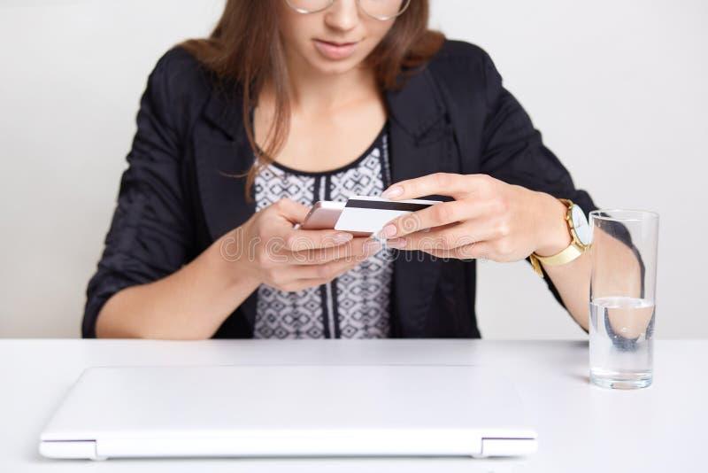 O tiro colhido do telefone esperto das posses fêmeas e do cartão plástico, espera o fim da verificação do cartão de crédito, faz  imagem de stock royalty free