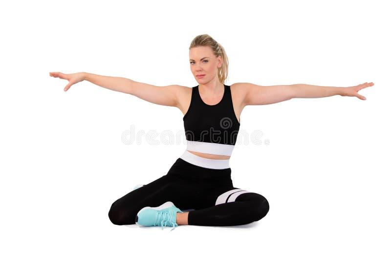 O tiro da jovem mulher flexível aquece-se no sportswear no estúdio na terra traseira branca - imagem foto de stock