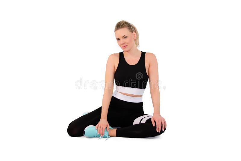 O tiro da jovem mulher flexível aquece-se no sportswear no estúdio na terra traseira branca - imagem imagens de stock royalty free