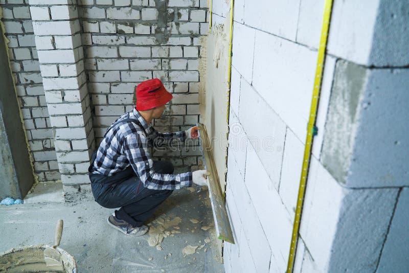 O tiro de ângulo alto do construtor que senta-se no seu hunkers o emplastro na parede do bloco imagem de stock