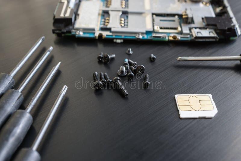O tiro do close up de um preto parafusa e desmontou o smartphone na superfície do preto foto de stock royalty free