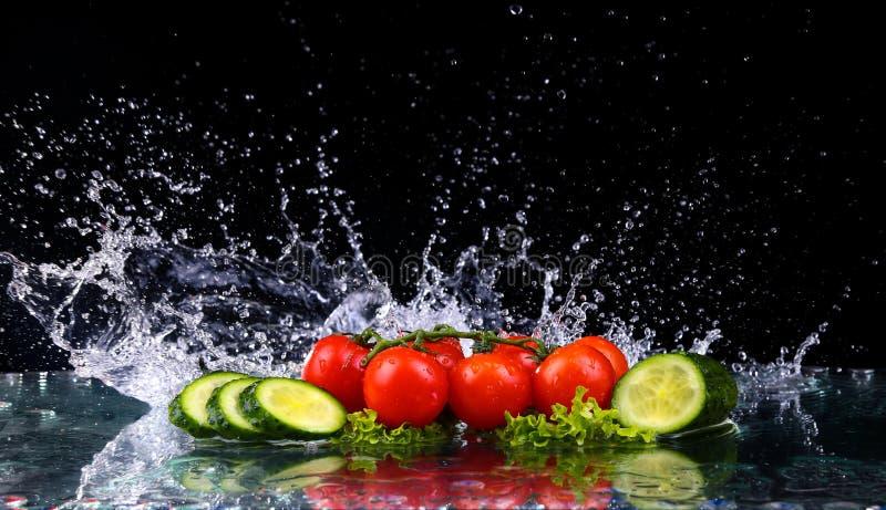 O tiro do estúdio com movimento do gelo de tomates de cereja e as fatias de pepino na água espirram no fundo preto imagens de stock royalty free