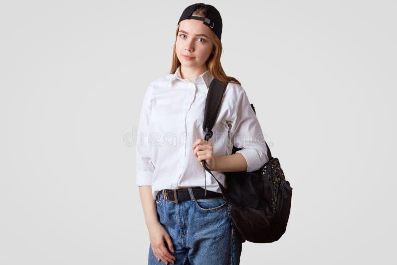 O tiro do estúdio da estudante consideravelmente bonita veste o jeand e a camisa branca, leva a mochila, está contra o fundo bran fotos de stock