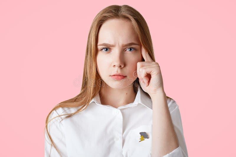 O tiro do estúdio da fêmea nova bonita séria mantém o dedo no templo, tenta recordar algo na mente, veste o shi formal branco foto de stock royalty free