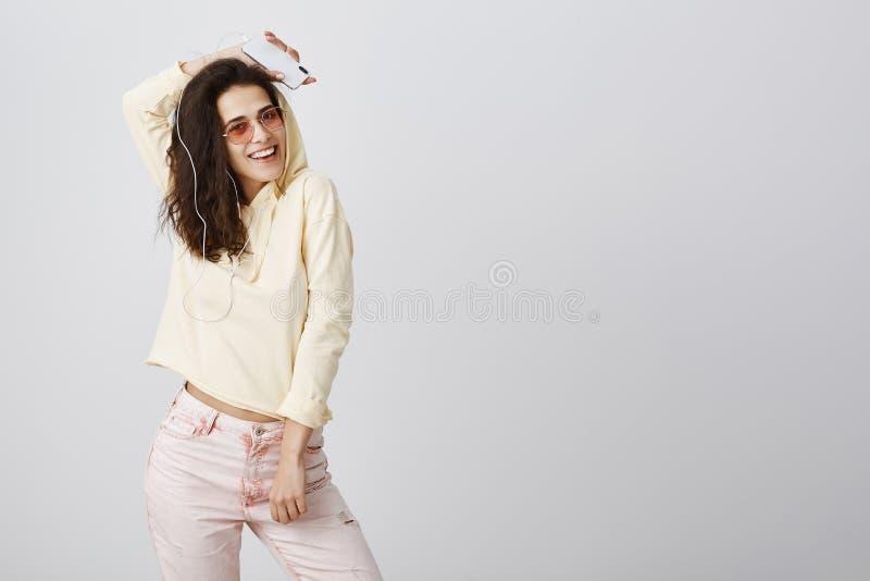 O tiro do estúdio da jovem mulher brincalhão expressivo com o cabelo encaracolado que levanta no amarelo colheu o hoodie e óculos imagem de stock