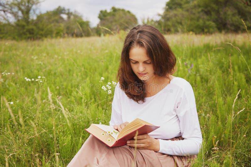 O tiro exterior da jovem mulher bonita séria aprecia o tempo do verão, senta-se no campo verde, lê livro interessante com grande  foto de stock