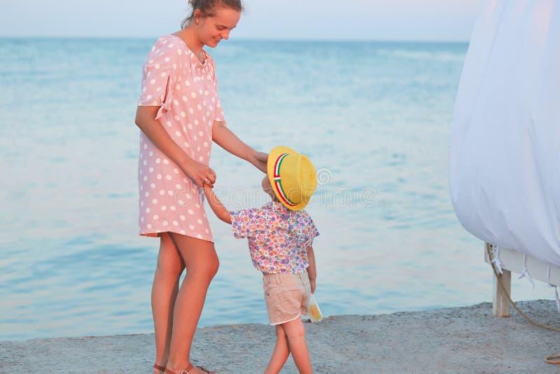 O tiro exterior da menina do andd da mãe tem a caminhada através do beira-mar, guarda as mãos, tem a conversa agradável, explica  foto de stock