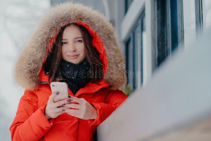 O tiro exterior da mulher caucasiano de cabelo escura bonita na roupa de rua do inverno, guarda o telefone celular moderno, lê a  fotografia de stock royalty free