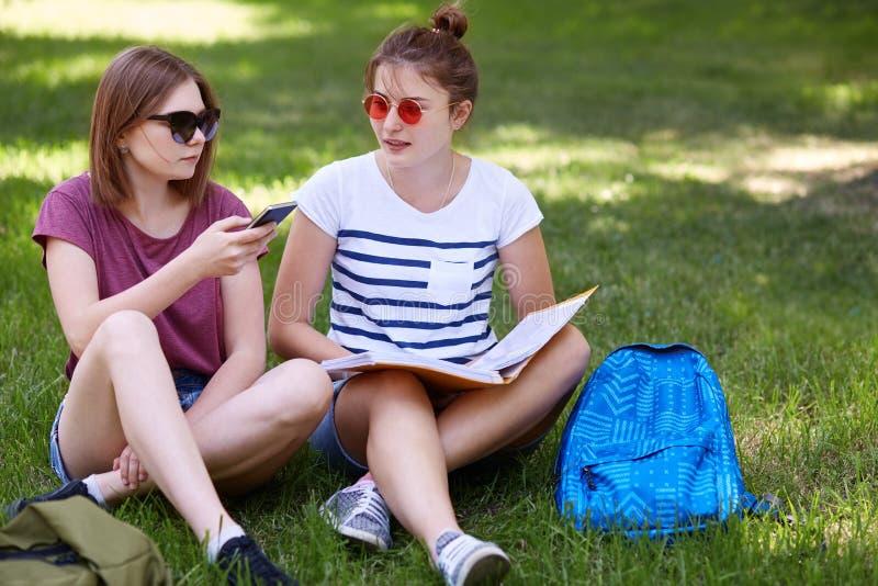 O tiro exterior de dois companheiros fêmeas, recreat junto contra a grama verde, senta os pés cruzados, usa o dispositivo moderno imagem de stock
