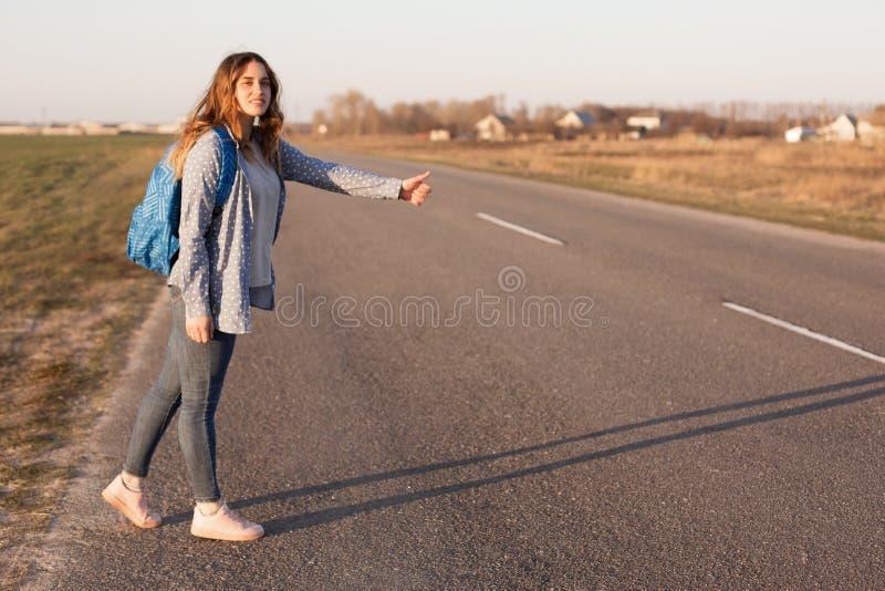 O tiro exterior do viajante fêmea consideravelmente de sorriso está na estrada, viaja e para carros, leva o saco, aprecia o estil fotos de stock royalty free