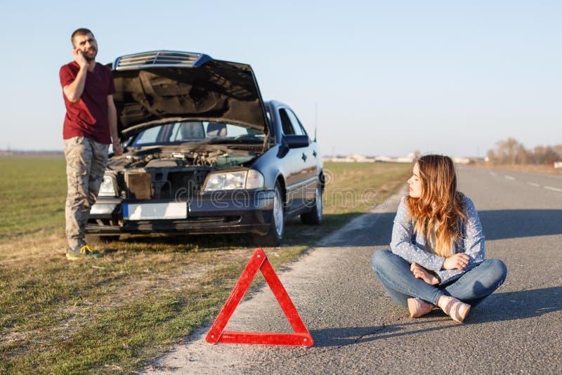 O tiro exterior dos pares perto do seu brocken o carro, o triângulo vermelho como o sinal de aviso, os suportes masculinos na fre fotografia de stock