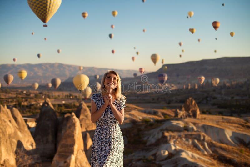 O tiro exterior horizontal da mulher de sorriso nova loura feliz no vestido que é entusiasmado como suportes na montanha alta olh foto de stock