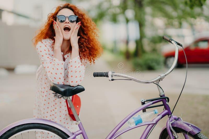 O tiro horizontal da bicicleta feliz dos passeios da mulher no parque, tem a ruptura, levanta na c?mera, mant?m a boca aberta, to fotos de stock royalty free