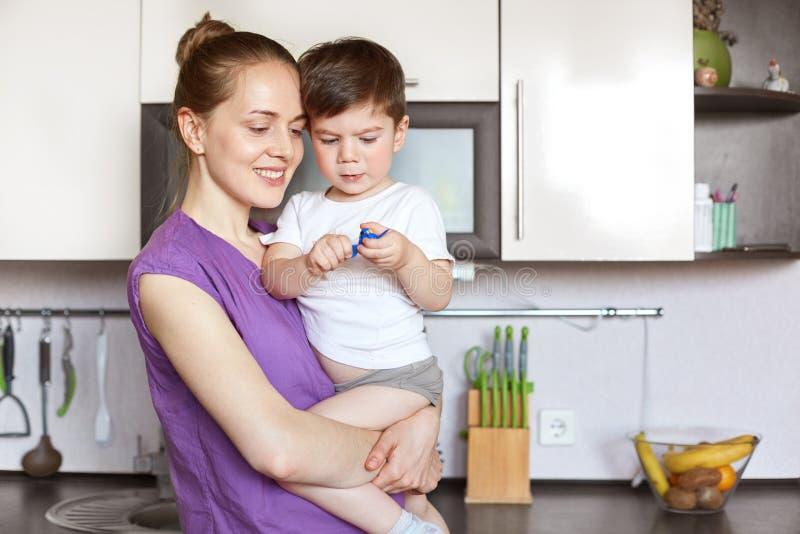 O tiro horizontal da fêmea de sorriso dos jovens bonitos guarda seu filho nas mãos, tem a expressão positiva, suporte contra o in imagens de stock