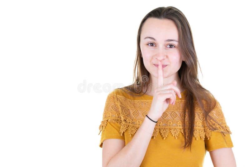 O tiro horizontal da jovem mulher bonita bonito mantém o dedo dianteiro nos bordos fotos de stock royalty free
