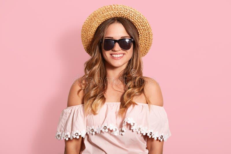 O tiro horizontal da jovem mulher bonita na camisa do verão com ombros e o chapéu desencapados do sol, olhando de sorriso na câme fotografia de stock royalty free