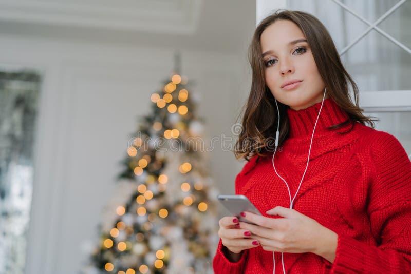 O tiro horizontal da menina europeia nova tem compor, pele saudável, cabelo escuro, vestido na camiseta desproporcionado, escuta  fotos de stock