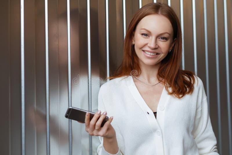O tiro horizontal da mulher alegre com cabelo tingido, sorriso toothy, conversa em linha através do smartphone, appliaction dos u imagens de stock