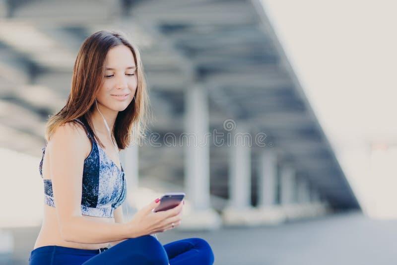 O tiro horizontal da mulher consideravelmente bonita com aparência agradável, escuta rádio, guarda o telefone celular moderno, us fotos de stock