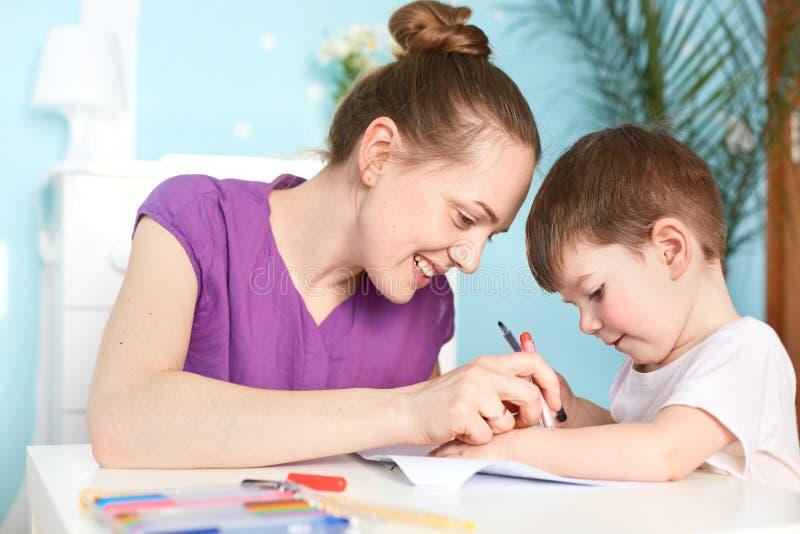 O tiro horizontal da mulher feliz com bolo do cabelo, menino pequeno, imagem da tração junto, pose contra interior doméstico, tem fotos de stock